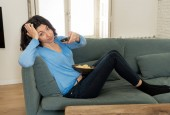 Fiatal ideges nő a kanapén segítségével ellenőrzés távoli Zapping unatkozik a rossz TV-műsorok és programozó. Keresi az érdektelen, zárkózott és álmatlan. Az emberek, túl sok a rossz televíziós és mozgásszegény életmód.