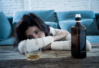 Drunk alcoholic depressed woman drinking scotch whiskey spirits alone at home. Feeling hopeless, week and lonely. In People lifestyle, Depression, alcohol addiction, alcoholism and drug abuse concept.