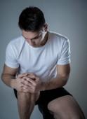 Mladý fit muž, který drží koleno s rukama v bolesti po utržení svalové bolesti v průběhu tréninku přerušené poranění nohou nebo křeče. V oblasti bolesti těla a sportovních cvičení a péče o tělo.