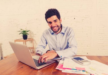 Happy attractive entrepreneur man calculating costs, charges, mortgage, taxes or paying bills with documents and laptop at home office. In online banking and Success business finances free of debts.