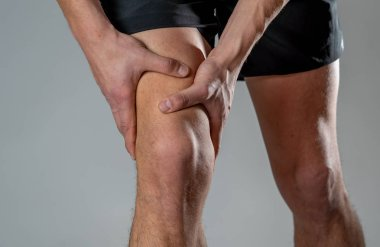 Young fit man holding knee with hands in pain after suffering muscle injury broken bone leg pain sprain or cramp during running workout. In Body pain and sport training injury and body health care.