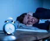 Ospalý a zoufalý mladý Kavkazan, který se v noci probudil a nemohl usnout, cítil se frustrovaný a ustaraný při pohledu na hodiny trpící nespavostí v konceptu stresu a poruchy spánku.