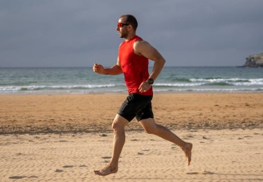Athlete runner running barefoot on beach at sunset. Sport man fitness model working out on sea shore in outdoors fitness training, sports, motivation and active healthy lifestyle concept.