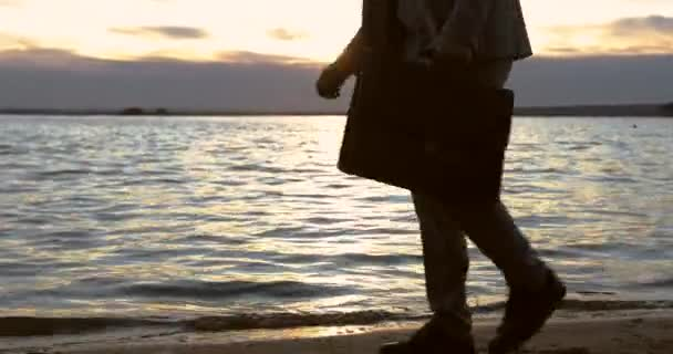 Businessman holding in hand briefcase and walking on the beach at sunset.