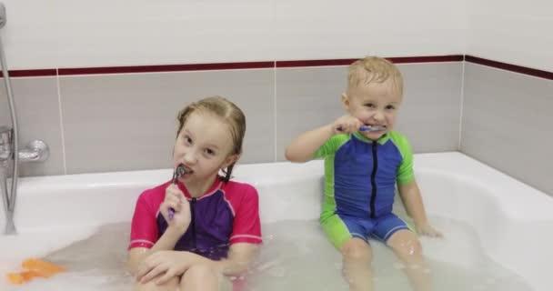 Junge und Mädchen putzen ihre Zähne sitzend im Wasser in der Badewanne.