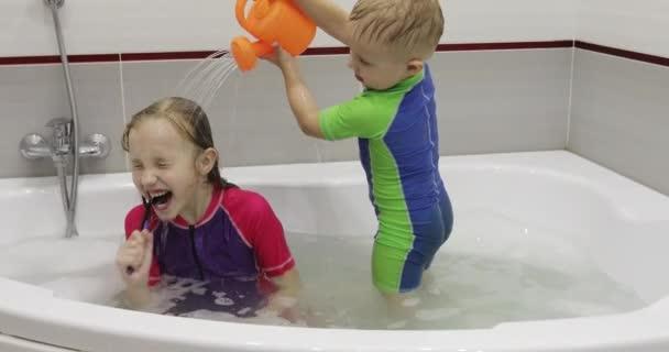 das Mädchen putzt sich im Wasser sitzend die Zähne in der Badewanne.