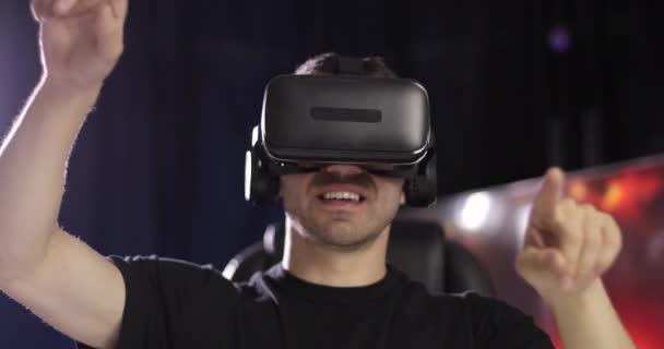 Der Mann in schwarzer Kleidung blickt mit Kopfhörern durch die VR-Brille und bedient sich virtueller Objekte und Karten.