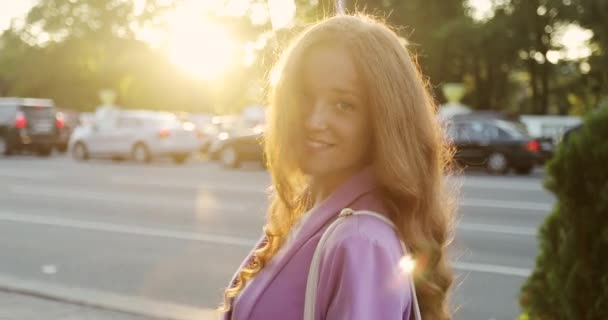 Portrait of happy girl with long red hair in city center during sunset.