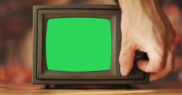 Egy férfi kéz hozzáér egy régi tévéhez..