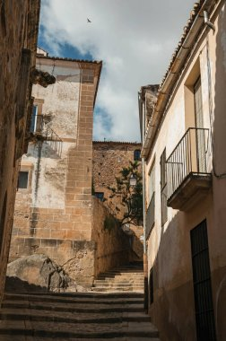 Narrow alley on slope with stairs and old stone buildings at Caceres