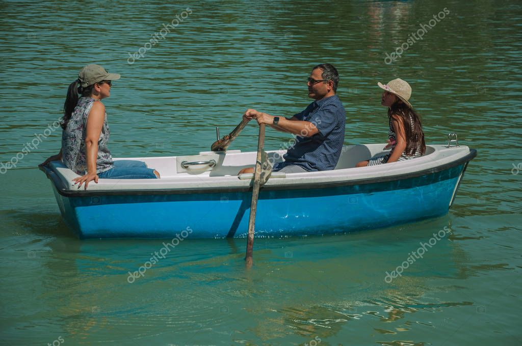 Family paddling boat in a park of Madrid