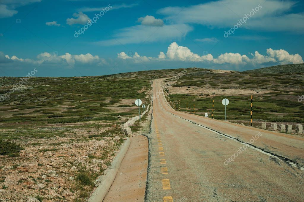 Roadway passing through rocky landscape and fields