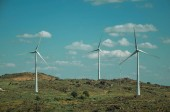 Mehrere Windräder über hügeliger Landschaft