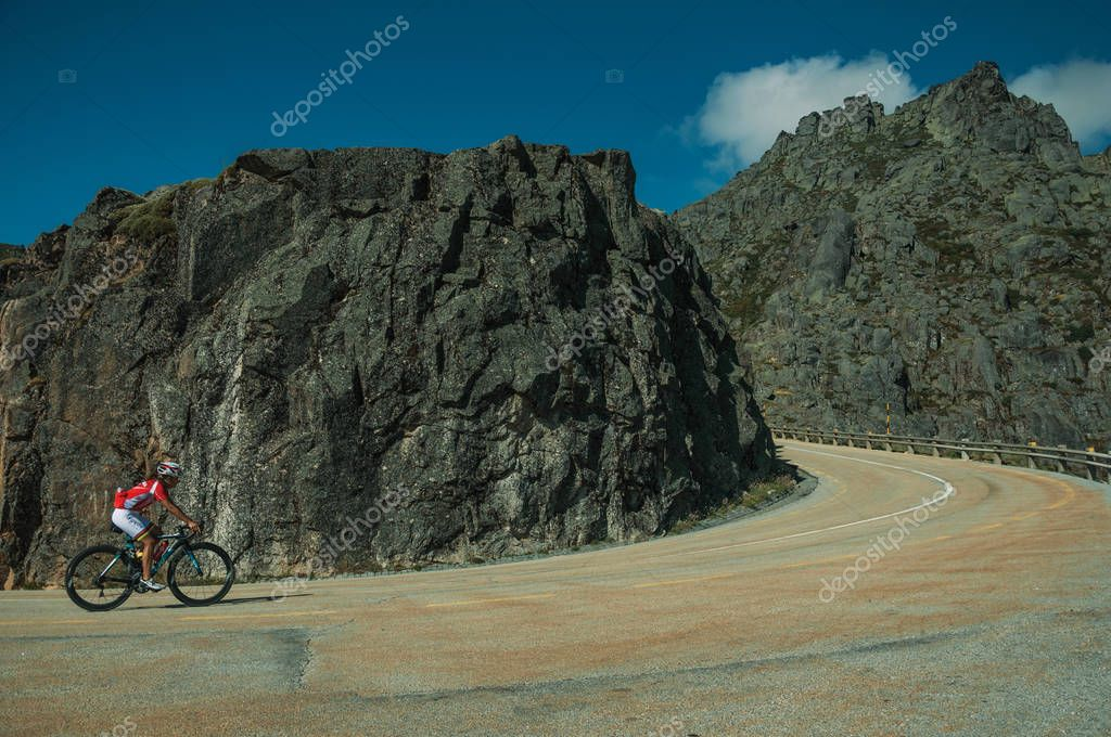 Road passing through rocky landscape with cyclist