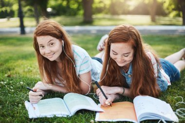 Homework are you kidding me. Two charming girls with red hair lying and chilling on grass during free time, doing homework, sister helping sibling with lessons, smiling and laughing