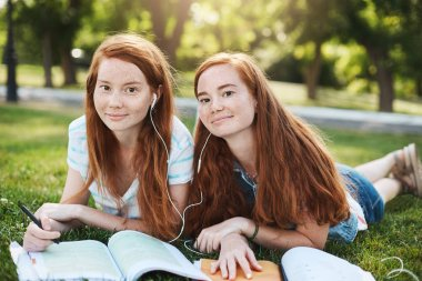 Girls make everything together. Charming natural redhead women in summer clothes lying on grass during weekends, sharing earphones to listen songs together, sister trying help with homework.