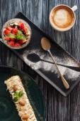 Fotografie pohled shora sladké chutné zákusky a kávu na dřevěný stůl