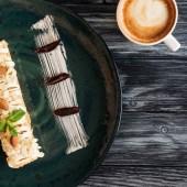 vergrößerte Ansicht des köstlichen Dessert mit Mandeln und eine Tasse Cappuccino auf Holztisch