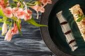 Fotografia vista superiore di delizioso dessert alle mandorle sulla piastra e fiori sulla tavola di legno