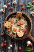 Fotografie top view of gourmet roasted eggs with cheese and fresh vegetables on wooden table