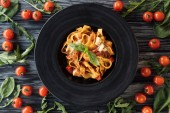 top view of delicious pasta on plate and fresh vegetables on wooden table