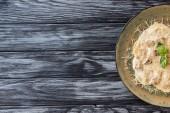 pohled shora na ravioli se špenátem a sýrem ricotta na štítku na dřevěný stůl