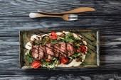 pohled shora labužnické plátky New York steak, zelenina a vidlice s nožem na dřevěný stůl