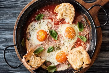 close-up view of gourmet fried eggs with cheese, bread and sauce in pan on wooden cutting board