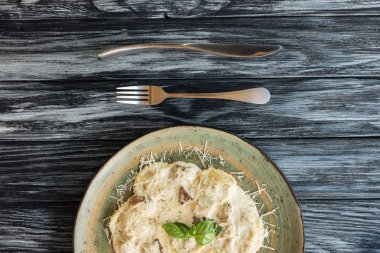 top view of delicious italian ravioli with cheese on plate and fork with knife on wooden table