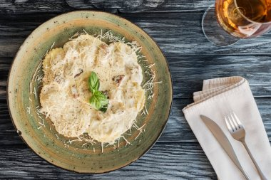 delicious ravioli with spinach and ricotta cheese, drink and fork with knife on wooden table