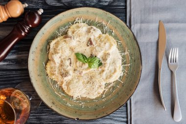 gourmet ravioli with spinach and ricotta cheese, spices and fork with knife on table