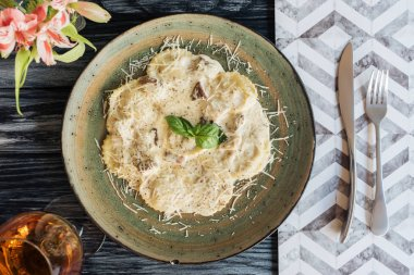 top view of gourmet italian ravioli on plate and fork with knife on wooden table