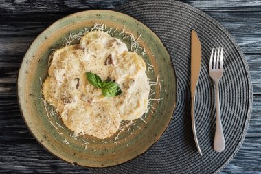 top view of delicious ravioli on plate and fork with knife on wooden table