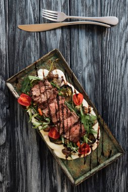 top view of delicious roasted sliced New York steak, vegetables and fork with knife on wooden table