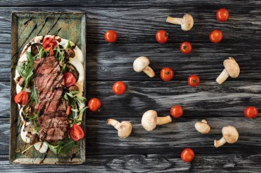 top view of gourmet sliced roasted steak with vegetables on wooden table