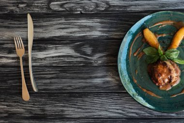 gourmet meat with sauce and basil leaves on plate, fork and knife on wooden table