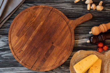 top view of empty wooden cutting board, spices, cheese and vegetables on table