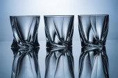 row of three empty whiskey glasses on grey with reflections