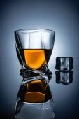 Fotografie Glas mit Whiskey und Ice Cube mit Reflexion, auf dunklen grauen Hintergrund