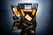Fotografie selektiven Fokus der zwei Gläser Cognac mit Eiswürfeln auf dunklen grauen Hintergrund