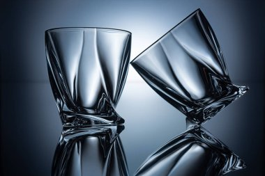 two transparent empty cognac glasses on grey with reflections