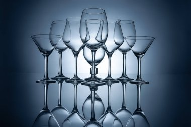 different empty wine glasses with reflections, on grey
