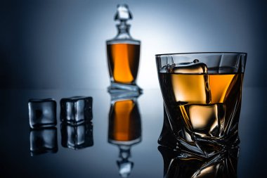selective focus of glass with cognac, ice cubes and bottle, on grey