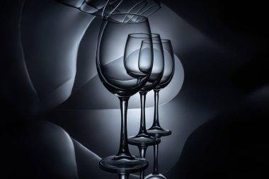 row on empty luxury wine glasses, dark studio shot