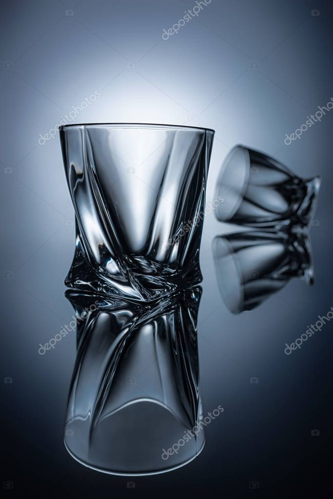 transparent elegant whiskey glasses on grey with reflections
