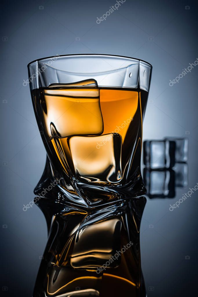 glass of whiskey with ice cubes with reflection, on dark grey background