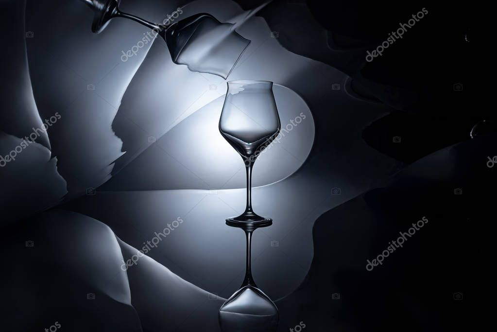 empty wine glass with geometric reflection on dark