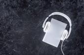 pohled shora bílé knihy a sluchátka na šedý stůl