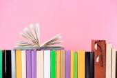 Photo open book and glasses on row of books isolated on pink