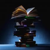 zásobník barevných knížek s otevřenou knihou na vrcholu na tmavý podklad